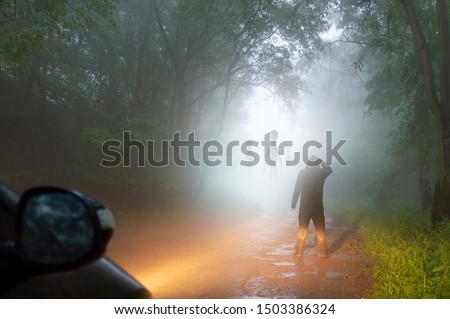 A science fiction concept of a man looking at aliens coming out the mist on a foggy, spooky forest road in the evening. Highlighted by car headlights. Royalty-Free Stock Photo #1503386324