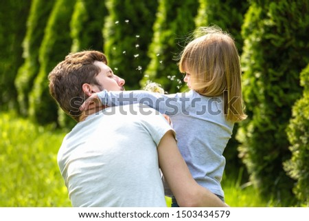 Back view. Father and daughter blowing dandelion flowers in sunny garden. #1503434579