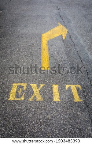 Exit sign with yellow painted arrow on the ground #1503485390