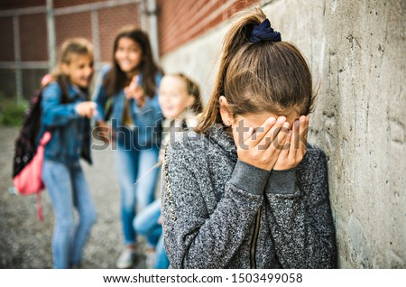 A sad girl intimidation moment on the elementary Age Bullying in Schoolyard #1503499058