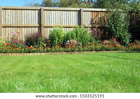 Shrubs And Flowers In A Border Surrounded By A Wooden Panel Fence And Grass Lawn In A Back Garden. Royalty-Free Stock Photo #1503525191