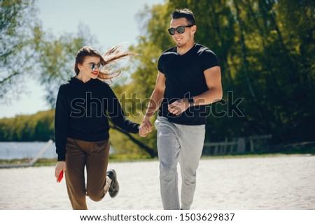 A stylish and bright love couple walks on the sunny beach #1503629837