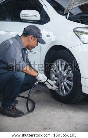 asian man is checking tyre of car for automotive maintenance service.motor car mechanic Inflate the tire at garage. #1503656105