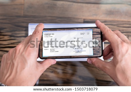 Man Taking Photo Of Cheque To Make Remote Deposit In bank Royalty-Free Stock Photo #1503718079
