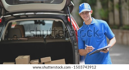 Delivery man checking orders for customer and smiling to the camera while standing in front of his car #1503743912