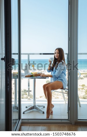 A beautiful young girl in a light blue shirt smiling broadly has breakfast on the balcony of the hotel on the seashore. Morning coffee at the hotel. Breakfast outside. #1503748676