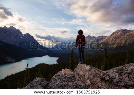 Adventurous girl standing on the edge of a cliff overlooking the beautiful Canadian Rockies and Peyto Lake during a vibrant summer sunset. Taken in Banff National Park, Alberta, Canada. #1503751925