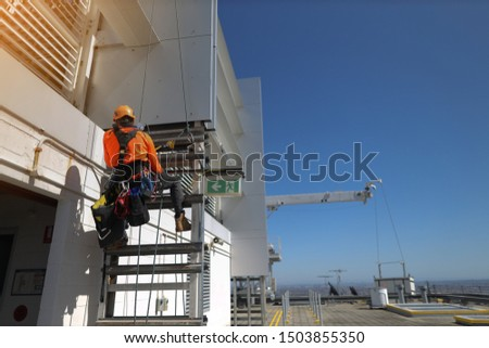 Rope access abseiler working at height installing exit sign at roof top in the emergency exit door construction site Sydney
