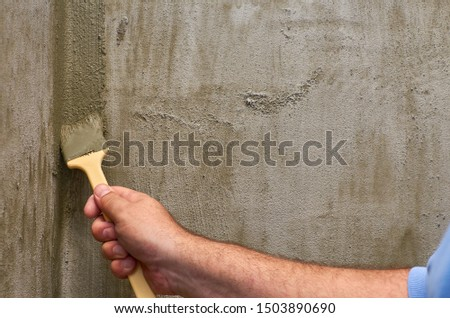 Applying layer of isolation material with a brush in a wall corner #1503890690