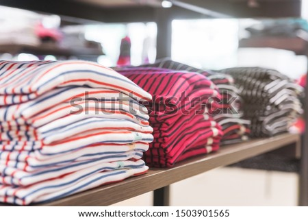 Colorful t-shirts on a shelf in a wardrobe boutique.Closeup picture.Wallpaper or billboard picture. #1503901565