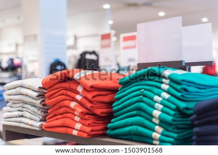 Colorful t-shirts on a shelf in a wardrobe boutique.Closeup picture.Wallpaper or billboard picture.Blurred background with space for text. #1503901568