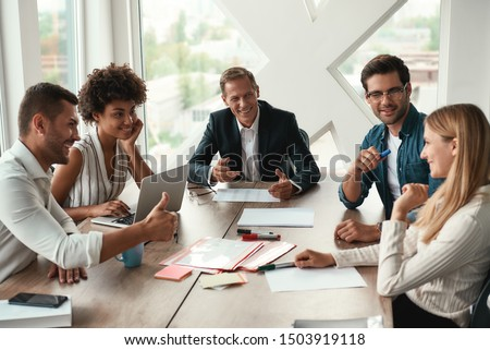 Teamwork. Multicultural team discussing something and smiling while sitting at the office table Royalty-Free Stock Photo #1503919118