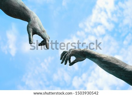 two hands, fragment of old statue. hands reaching each other with fingers against sky background. touch, contact, art minimal symbol. Creation of Adam metaphor by Michelangelo #1503930542