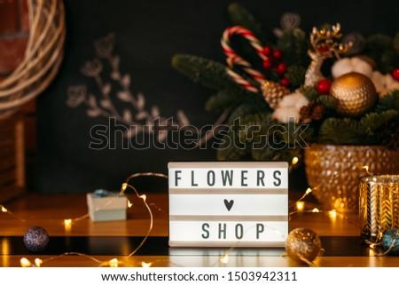 Florist workplace. Flowers shop sign plate and fairy lights over blur fir tree arrangement. #1503942311