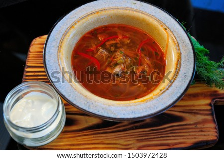Traditional Russian borsch soup with fried carp made in Mordovian style and served with smetana sour cream #1503972428