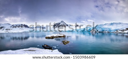 Panarama of the mountains, snow and blue glacial ice of the Smeerenburg glacier, Svalbard, and archipelago between mainland Norway and the North Pole. An inflatable boat is anchored in the foreground, Royalty-Free Stock Photo #1503986609