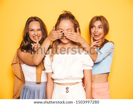 Three young beautiful smiling hipster girls in trendy summer clothes.Sexy carefree women posing near yellow wall in studio.Models surprising their friend.They cover her eyes and hugging from behind #1503997280