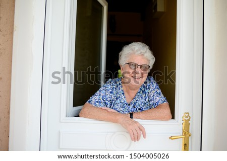 elderly senior woman opening front door of house and welcoming people at home  #1504005026