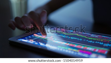 Finger touch on tablet computer with stock market data #1504014959
