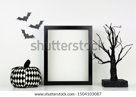 Mock up black frame with pumpkin and spooky tree decor on a shelf or desk. Halloween concept. Portrait frame against a white wall with bats.
