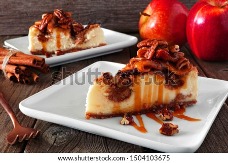 Caramel apple pecan cheesecake slices. Side view table scene with a rustic wood background. Autumn dessert. Royalty-Free Stock Photo #1504103675