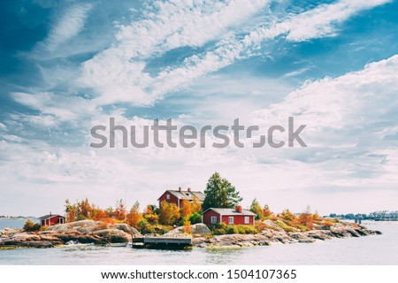Suomi Or Finland. Beautiful Red Finnish Wooden Log Cabin House On Rocky Island Coast In Summer Sunny Evening. Lake Or River Landscape. Tiny Rocky Island Near Helsinki, Finland. #1504107365