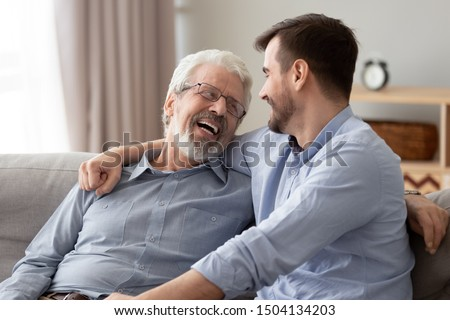 Happy two generations male family laugh enjoy talking bonding embracing sit on sofa at home, old senior father and young adult grown son relaxing having fun hugging chatting on couch on fathers day #1504134203