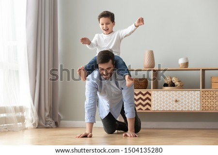 Happy funny family excited little boy playing with father at home, young dad crawling on floor carrying cute small child son on back giving kid piggyback ride having fun spending time together #1504135280