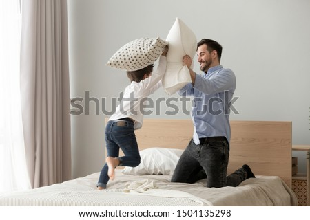 Funny small kid son playing pillow fight with dad on bed, happy cute little child boy and young father having fun in bedroom enjoying family leisure morning lifestyle activity together at home