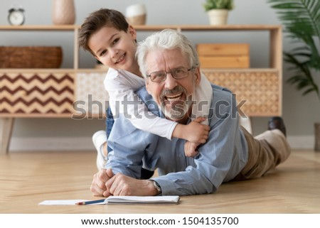 Happy two 2 generations family old grandfather and cute little boy grandson drawing with pencils lying on warm heated wooden floor together, smiling senior grandpa play with grandchild look at camera