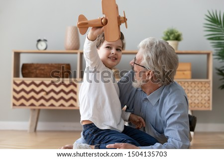 Happy two 2 generation family old grandfather and cute little child boy grandson play hold wooden toy plane lay on floor, funny small grandkid having fun with grandpa fly on airplane laughing at home #1504135703