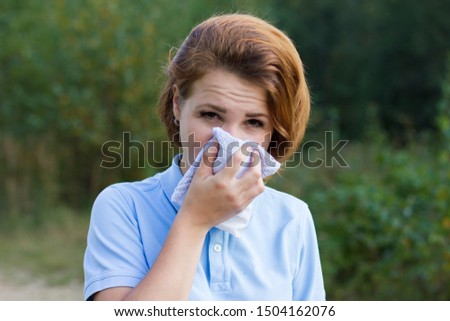 Sick ill beautiful girl blow her nose in a scarf, suffering from allergy, having a pollen allergy. Woman covers her nose from dust outdoor. Environmental pollution. Natural green background, in forest #1504162076