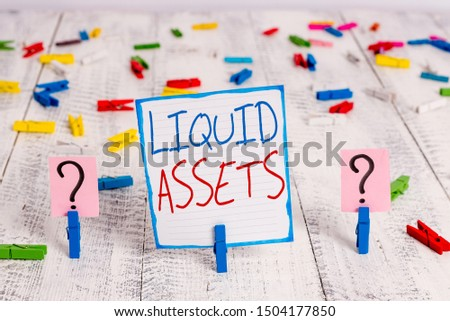 Conceptual hand writing showing Liquid Assets. Business photo showcasing Cash and Bank Balances Market Liquidity Deferred Stock Crumbling sheet with paper clips placed on the wooden table. #1504177850