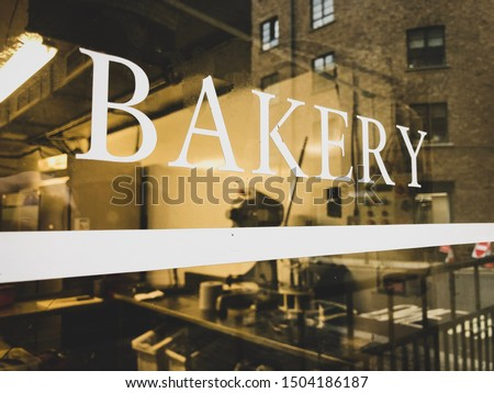 Looking through a bakery window from the outside. Storefront sign on the glass with reflection of the city street.