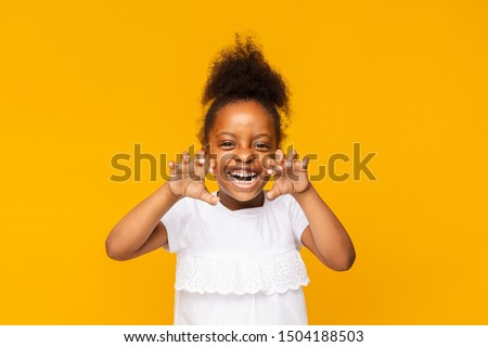 Funny tiger. Cute playful little african girl is showing claws, orange studio background #1504188503