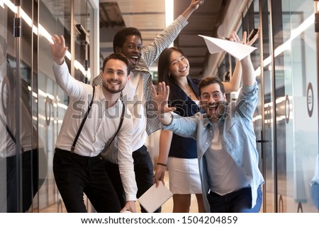 Overjoyed funny multiracial millennial employees look at camera having fun in office hallway, happy excited multiethnic diverse work group, young motivated team posing for picture in corridor Royalty-Free Stock Photo #1504204859