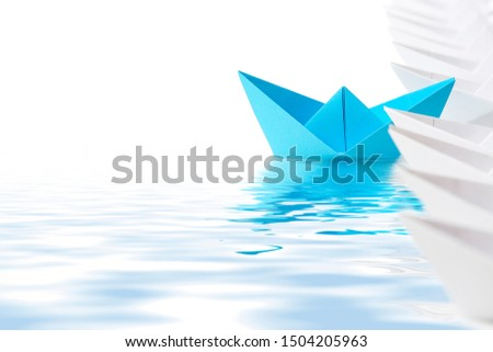 blue paper boat leading the race against white ones #1504205963