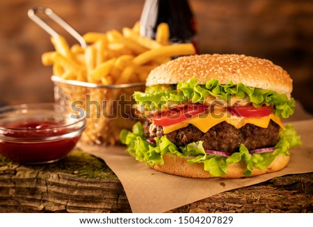 Hamburger with cheese and fried potatoes on a wooden table