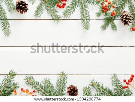 Christmas frame made of fir tree branches, red berries, pine cones on rustic wooden white background. Christmas, New Year, winter holidays concept. Flat lay, top view, copy space #1504208774