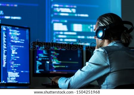 Software developer freelancer man male in headphones work with program code C++ Java Javascript on wide displays at night Develops new web desktop mobile application or framework. Projector background #1504251968