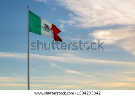 COZUMEL, MEXICO: mexican flag waving in sunset sky in Cozumel. #1504293842