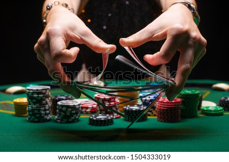 Girl dealer or croupier shuffles poker cards in a casino on the background of a table, chips,. Concept of poker game, game business #1504333019
