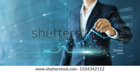 Businessman draw growth graph and progress of business and analyzing financial and investment data ,business planning and strategy on blue background. Royalty-Free Stock Photo #1504342112