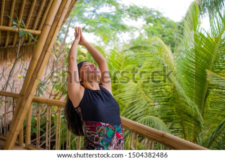 young natural and attractive Asian Chinese woman practicing yoga and meditation exercise outdoors at beautiful wooden joglo studio with tropical jungle view in wellness and healthy lifestyle #1504382486