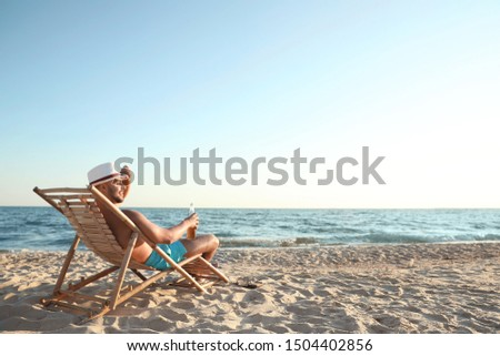 Young man relaxing in deck chair on beach near sea #1504402856