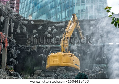 Excavator, cutter demolishing old building  Royalty-Free Stock Photo #1504415453