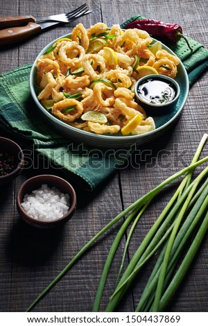Japan fast food: fried squid rings served in a blue plate with soya sauce, scallion, lemon, lime, chile pepper, on a dark wooden table, close-up, vertical