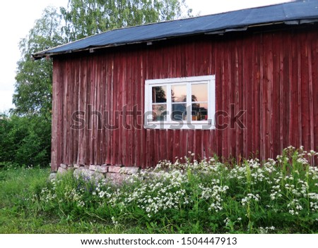 an old barn in the countryside of northern Sweden pictured in the middle of the midsummer night, the midnight sun is reflecting in the window
