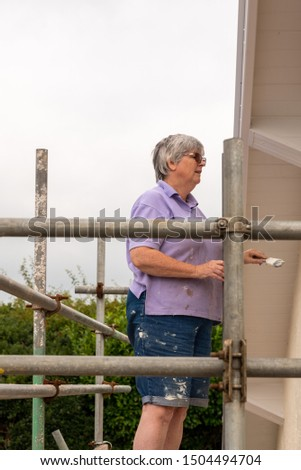 Woman painter stood on scaffolding painting a house wall with cream paint #1504494704