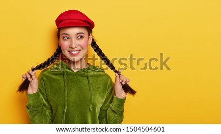 Good looking brunette woman holds two pigtails, looks away with happy expression, thinks about interesting choice, recalls lovely moment in life, wears red cap and green jumper, smiles pleasantly #1504504601